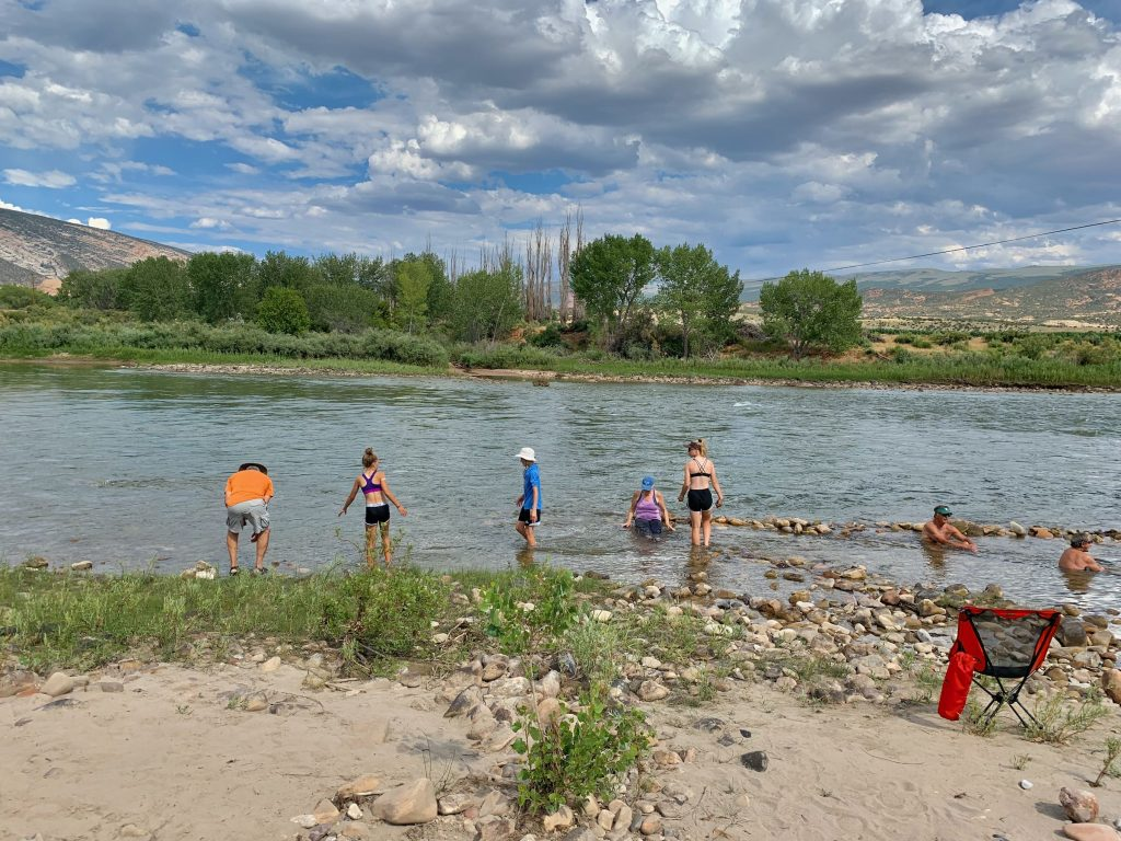 family wades in Green River in Dinosaur National Monument